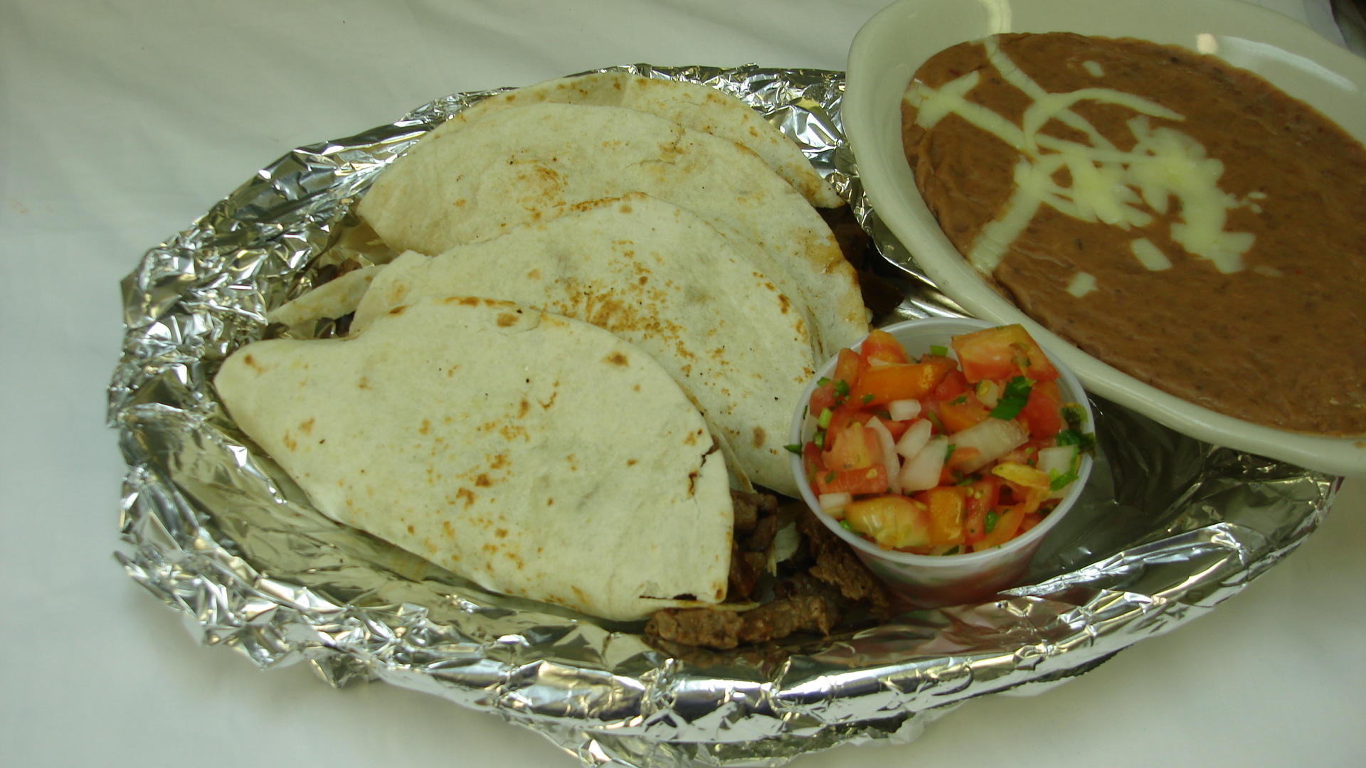 Tacos de Carne Asada - Three flour tortillas stuffed with grilled steak. Served with pico de gallo and beans.