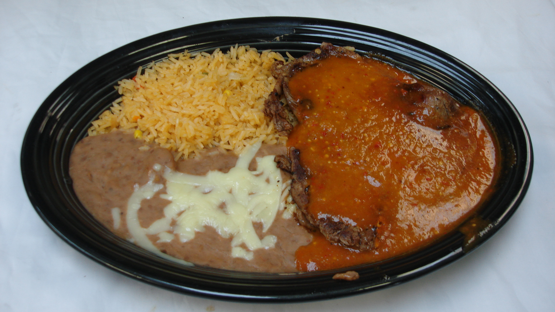 Steak Ranchero - Grilled 10 oz. T-bone steak cooked with our spicy special sauce and served with rice and beans.